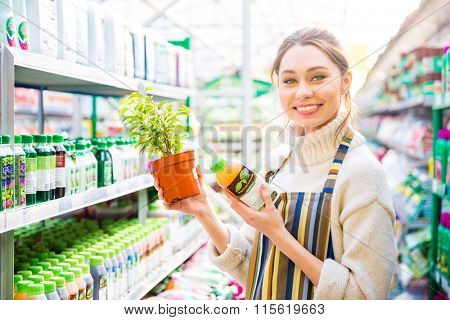 Happy charming young woman gardener buying agricultural chemicals for plants in shop