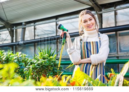 Smiling beautiful young woman standing in orangery and holding garden hose
