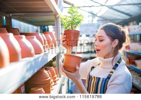 Pensive charming young woman gardener choosing new pot for her plant in store