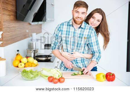 Happy young couple cooking and hugging on the kitchen