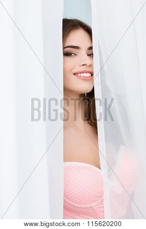 Happy playful young woman in pink corset hiding behind white curtains and smiling