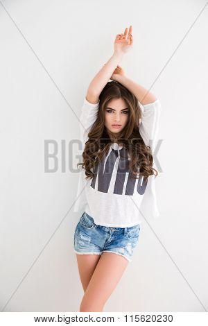 Beautiful young female with curly long hair posing with raised hands over white background