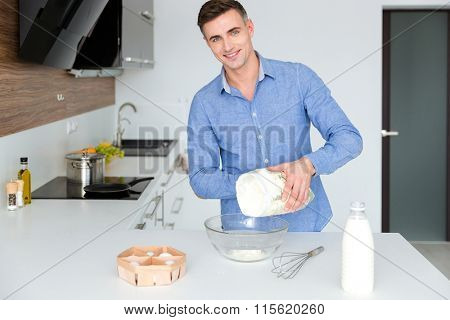 Happy handsome man in blue shit standing and cooking on the kitchen