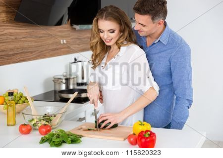 Beautiful couple making vegetarian salad and flirting on the kitchen