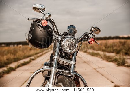 Motorcycle on the road with a helmet on the handlebars.