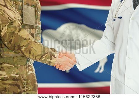 Military Man In Uniform And Doctor Shaking Hands With Us States Flags On Background - Wyoming