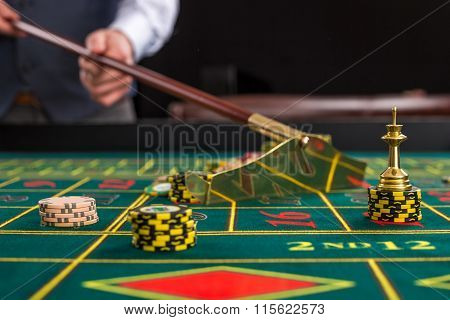 Close up of gambling chips on green table in casino.