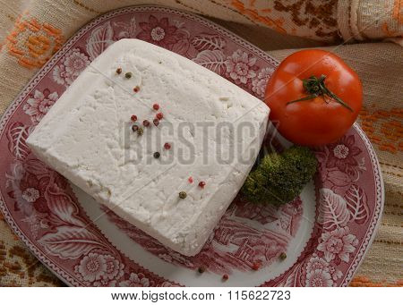 whole piece of goat cheese on a red dish