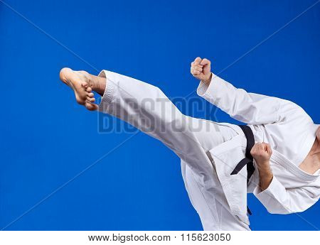 On a blue background athlete beats kicking