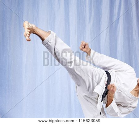 On a light background a man beats a high kick