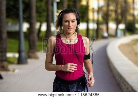 Young Blonde Sportswoman Running In Park