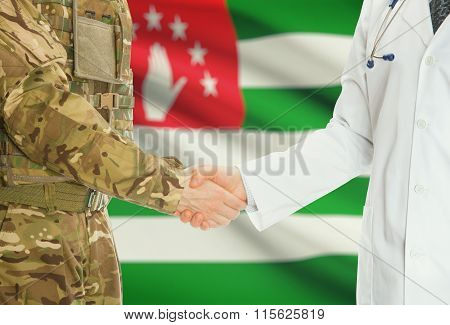Military Man In Uniform And Doctor Shaking Hands With National Flag On Background - Abkhazia