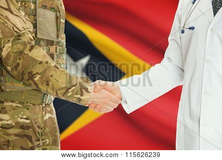 Military Man In Uniform And Doctor Shaking Hands With National Flag On Background - East Timor