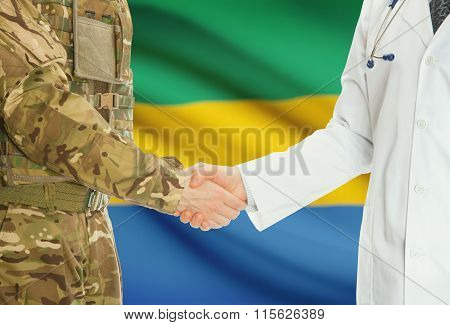 Military Man In Uniform And Doctor Shaking Hands With National Flag On Background - Gabon