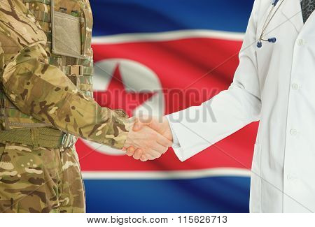 Military Man In Uniform And Doctor Shaking Hands With National Flag On Background - North Korea