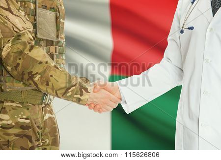 Military Man In Uniform And Doctor Shaking Hands With National Flag On Background - Madagascar
