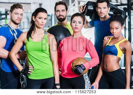 Group of women and men in gym posing at fitness training standing together with gear and dumbbells