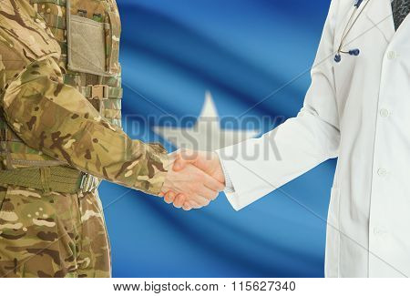 Military Man In Uniform And Doctor Shaking Hands With National Flag On Background - Somalia