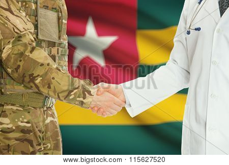 Military Man In Uniform And Doctor Shaking Hands With National Flag On Background - Togo