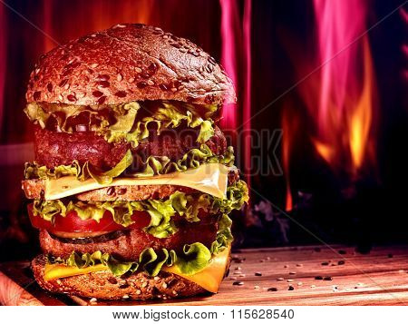 Huge double patty hamburger  board on background of fire.