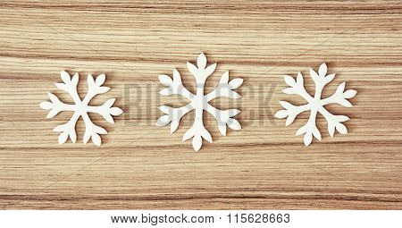 Group Of White Snowflakes On The Wooden Background