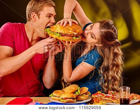 Woman and man feed each other fast food. Concept.