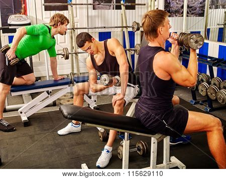 Group of strong men hard working on simulator his body at gym.