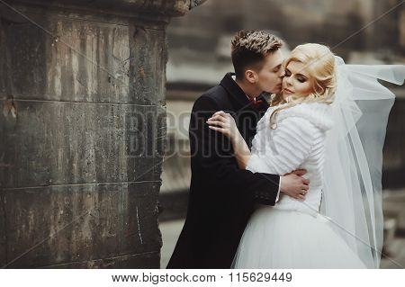 Gorgeous Newlywed Bride In White Coat And Handsome Groom Valentynes Kissing In Front Of Old Baroque