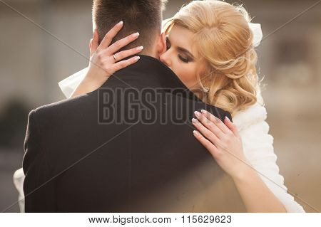 Beautiful Blonde Bride Kissing Handsome Groom In Black Coat In The Streets Face Closeup