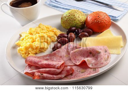 Breakfast with sausages, scrambled eggs, cheese, olives, black coffee, and colored buns