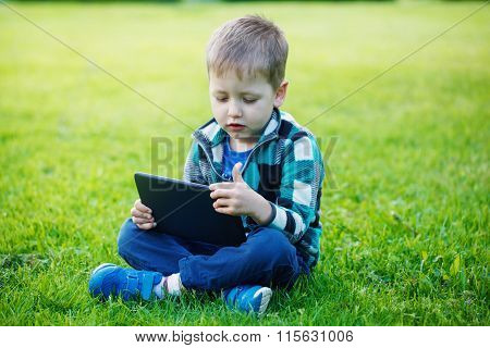 Little Boy With Tablet Sit On The Grass