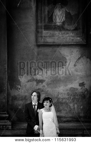 Romantic Sensual Husband And Wife Posing In Front Of Old Church Wall B&w