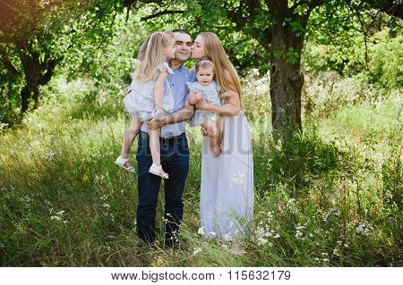 Mom and dad playing on the nature and hugging two daughters