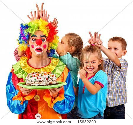 Clown holding cake on birthday with group children putting horns. Isolated.