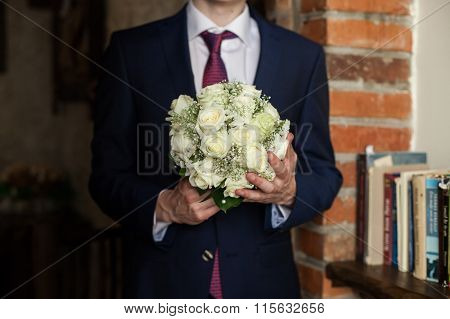 Handsome Groom In Stylish Black Suit And Red Tie Holding White Bouquet Closeup