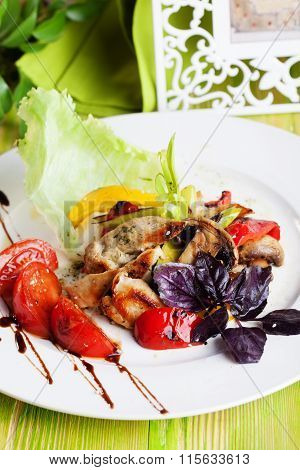 Beautiful salad with grilled chicken, mushrooms, vegetables, peppers, leeks in a still life on green