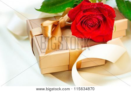 Rose and Gift box. Valentine's Day Red Rose and gift with silk bow over silk background. Wedding or Valentines Gift. Art design with flower and golden satin ribbon closeup.