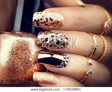 Golden Nail art manicure. Holiday style bright Manicure with gems and sparkles. Bottle of  Nail Poli