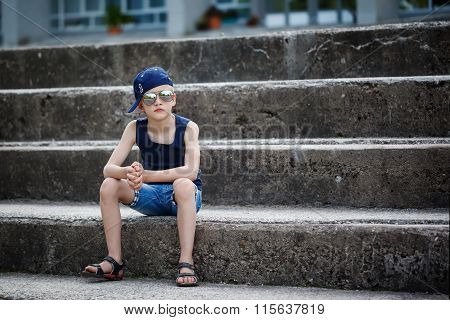 Portrait Of Fashionable Little Boy In Sunglasses And Cap Siting