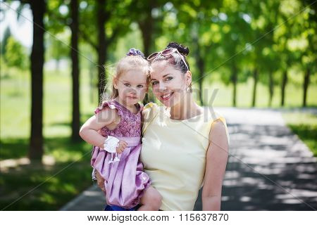 Happy Family. Mother And The Daughter Look At Camera, Smile, Emb