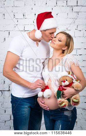 Young Pregnant Family. Husband Kisses His Wife. Concept New Year And Happy Pregnancy.