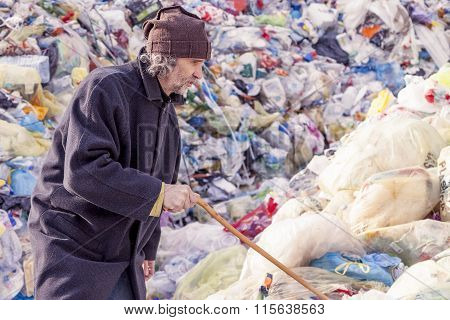 homeless man digs in the garbage