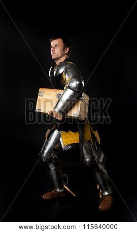 Medieval knight carrying a treasure chest
