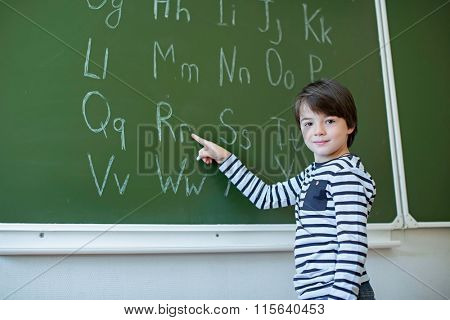 Little schoolboy with alphabet on a blackboard