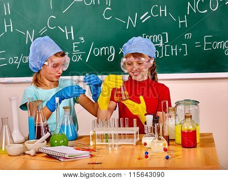 Happy children holding flask do experiments in chemistry class.