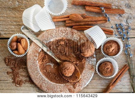 Making chocolate truffles. Homemade round chocolate candies with cocoa powder, almonds and cinnamon