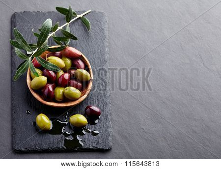 Fresh olives with leaves on a black board