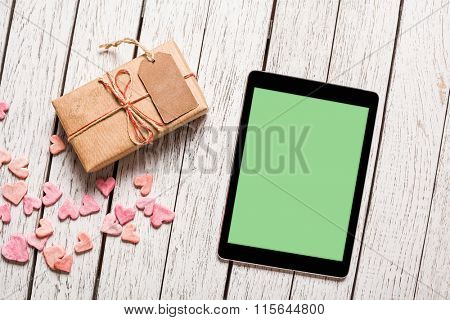 Digital tablet computer and vintage gift box with gift tag on white wooden background. Clipping path included.