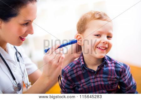 Female doctor examining little child boy. Horizontal view of boy during ear examination
