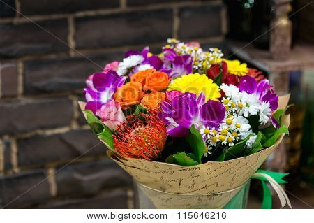 Flowers bouquet with Leucospermum, roses and orchids.